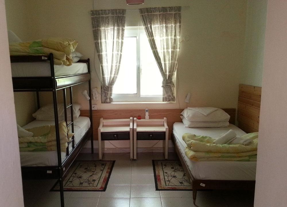 מיטת קומותיים ומיטה בודדת ואמבטיה בחדר